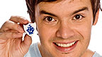Blue Peter presenter Barney Harwood holding a Blue Peter badge