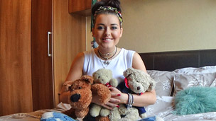 shannon sitting on her bed holding teddy bears.