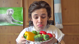 Cel Spellman holds up a plate of vegetables, looking sceptical.
