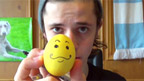 Cel holding up an egg with a smiley face drawn on it.