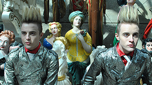 Jedward stand infront of many colourful statues looking pensive