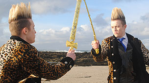 Jedward pretend to fight with swords on the shore of Skara Brae.