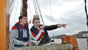 Jedward and Richard Wisker pointing on a boat on the Thames.