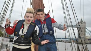 Jedward and Richard Wisker on a boat with Tower Bridge.