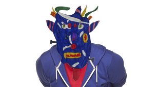 A blue, clown like monster head stuck onto Chris' face.