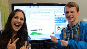 Chris and Jess infront of a TV screen with the Messageboards on