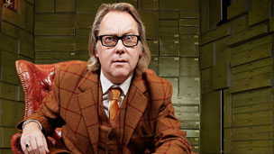 Vic Reeves sat in a chair.
