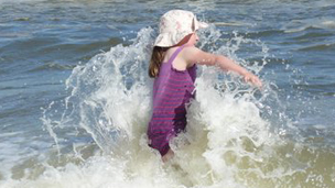 A girl plays in the sea.