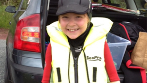 A girl in a wet-suit and life-jacket