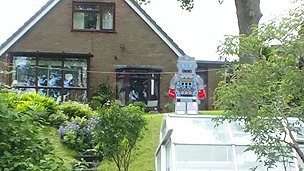 A really big robot sat on a greenhouse in the garden, using a perspective technique.