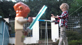 A photo of a toy close to the camera so it looks like it's sword fighting with a kid in the background