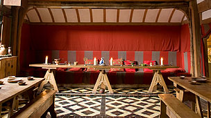 A medieval table set with jugs and pots in an ornate dining room.