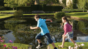 Two children running across the gardens at Bateman's