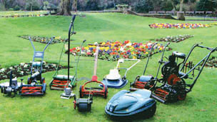 A collection of vintage lawnmowers in a garden.