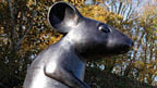 A mouse statue in front of trees.