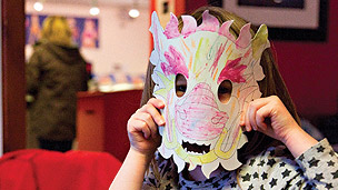 A child wearing a mask coloured in with crayons.
