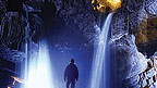 A man standing in a vast cave with waterfalls.