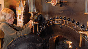 A child trying out part of a steam engine