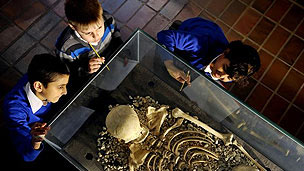 Three schoolboys looking at the remains of a Roman skeleton in a glass case.