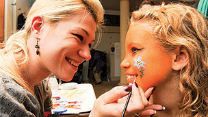 A girl having her face painted by a woman