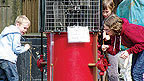 Two children playing with a red steam pumping engine