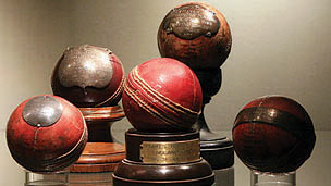 Five old cricket balls on stands, one is engraved.