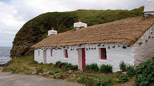 A white cottage with thatched roof at Niarbyl.