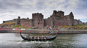 A longboat race taking place in front of Peel Castle.