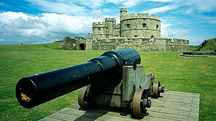 A Large cannon in the foreground with Pendennis Castle in the distance.