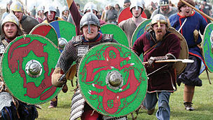 A group of angry vikings running towards the camera, one has a shield and a ginger beard.
