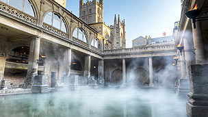 The roman baths with steam rising from the water.