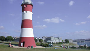 A view of Smeaton's Tower, a red and white striped lighthouse with blue sky in the background.