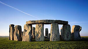 A wide view of Stonehenge with a bright blue sky in the background.