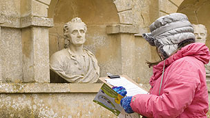 A young girl writing on a clipboard while looking at ornamental statue heads.