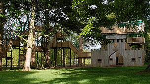 An outdoor play fort surrounded by trees.