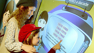 Two girls playing an interactive quiz about the Beatles on a screen.