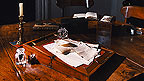 An oak writing desk with letters, and ink pot and quill placed on it.