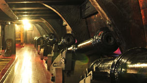 Cannons lined along the inside wall of a wooden ship.