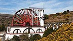 The large water wheel at Laxey Mines, red next to a large white building.