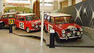 Three mini coopers are on a red podium crossing a finish line.