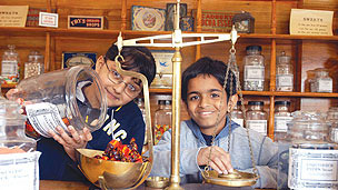 Two young children weigh sweets in a old fashioned sweet shop.