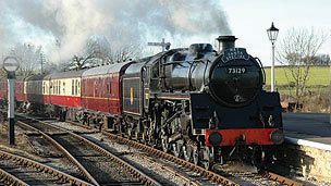 A large black and red steam train coming towards the camera.