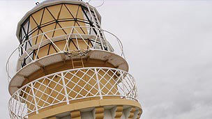 The top part of a beige lighthouse.