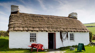 A traditional white cottage with thatched roof
