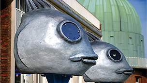 Two sculpted metalic fish heads on a wall.