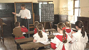 A school teacher dressed in a Victorian outfit teaching school children in an old classroom with a blackboard and desks.