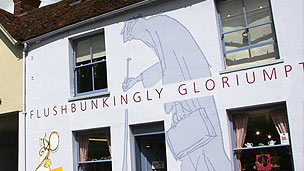 The exterior of the Roald Dahl Museum, a white building with an image of the BFG painted on it.