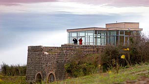A viewing station situated on a hillside with two people looking out of the large windows.
