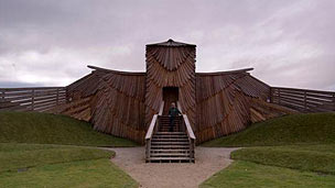 A large wooden building in the shape of a sparrow with wings spread.