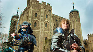 Two boys stood infront of the Tower of London, one wearing medieval armour, the other wearing samouri armour.